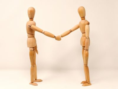 2 wooden people shaking hands
